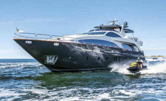 Man riding a jetski next to a large yacht
