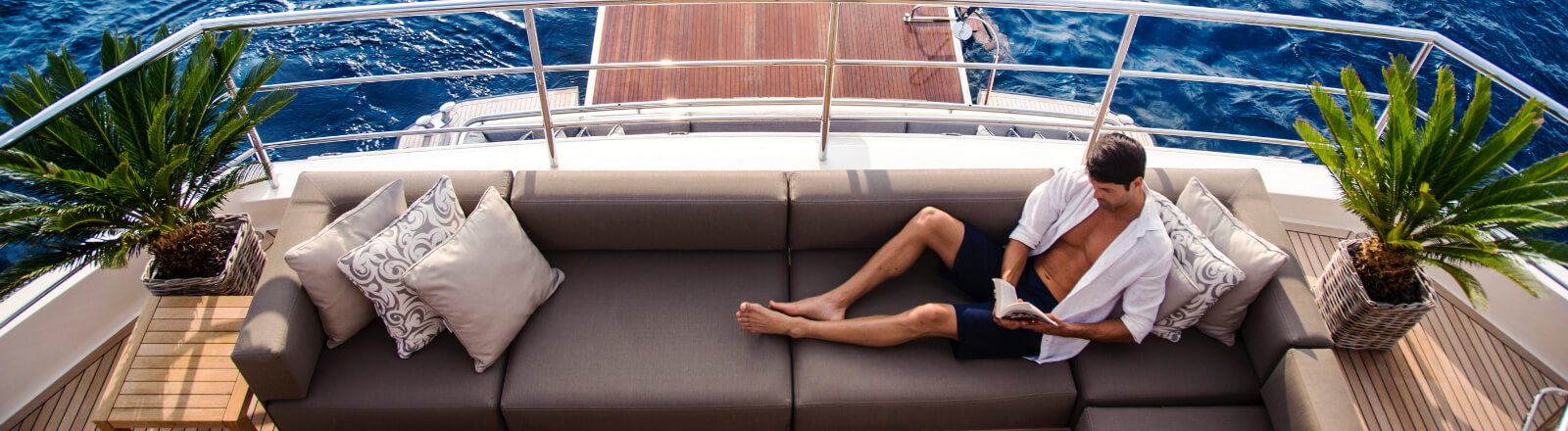 Man relaxing on sofa on the back of a yacht reading a book