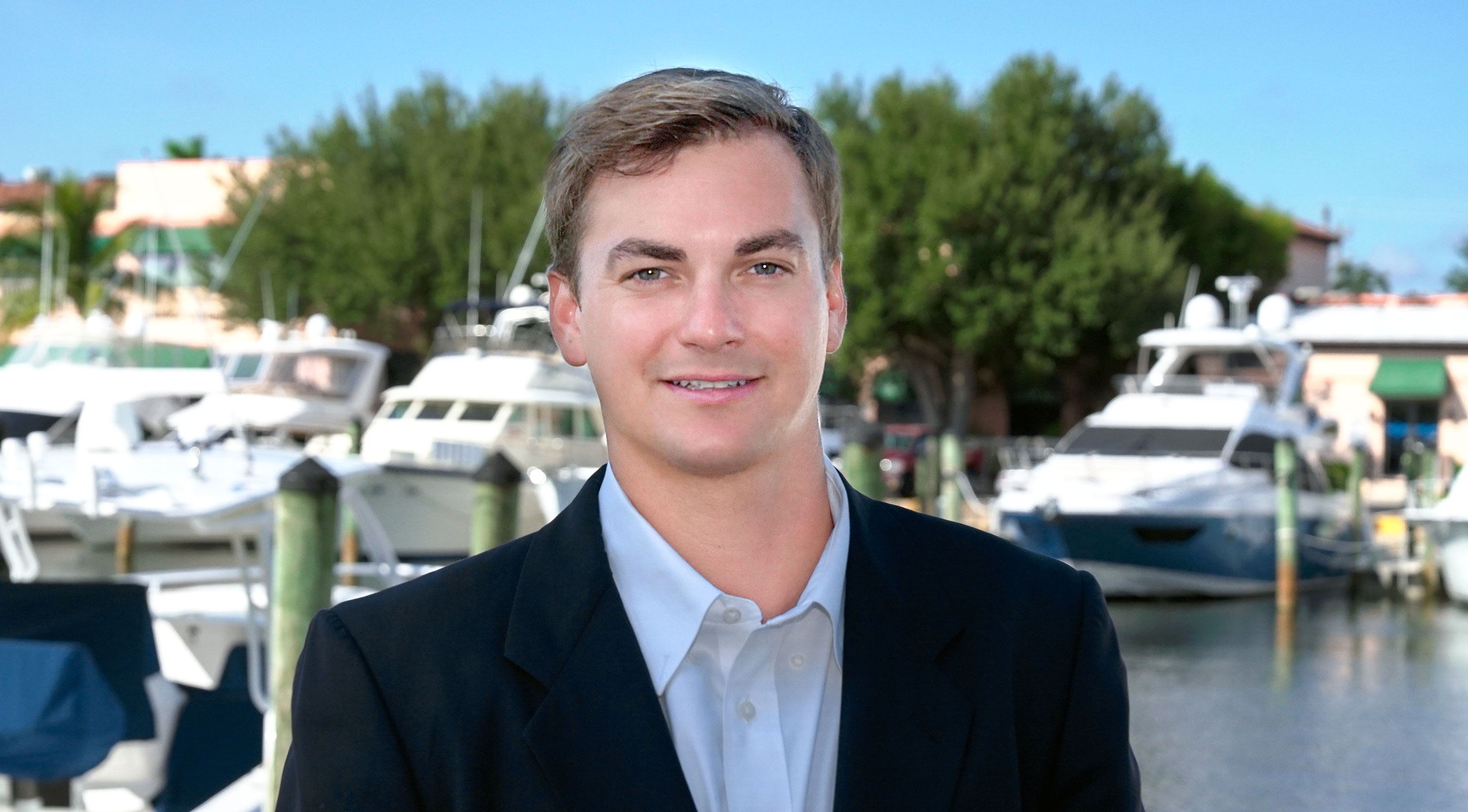 Forrest Robertson standing in marina with yachts behind him